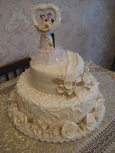 3-х ярусный торт с украшением из белых цветов с фигурками жениха и невесты