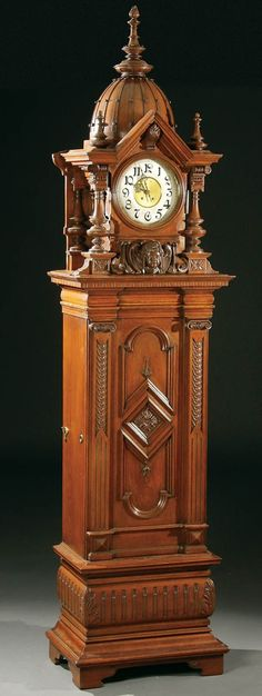 """A RARE SYMPHONION TRIPLE DISC """"EROICA"""" MUSICAL CARVED OAK LONGCASE CLOCK German, circa 1895, the three 13 5/8 inch discs each playing on two combs driven in harmony by two spring motors below a Lenzkirch """"1 Million"""" movement. The case with domed top flanked by turned pillars above a carved winged cherubs head. Together with 42 sets of three discs, plus extra incomplete sets. Height 104 inches. Sold for $78,000."""