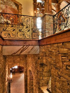 The staircase leads to the lower level and has custom designed wrought iron rails with decorative leaves and acorns, along with hand scraped walnut hard wood floors and masonry stone walls. The floors were hand scrapped by the Amish.