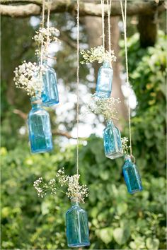 From Wedding Chicks: hanging blue bottles make excellent decor for a wedding inspired by a vintage sapphire engagement ring!