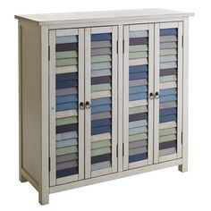 Country cottage meets seaside retreat in this fun, versatile four-door cabinet. Mismatched louvre doors with metal ring-pulls mimic the look of salvaged architecture. Inside are four roomy adjustable shelves for storage.
