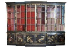 Chinoiserie breakfront by Union National Furniture of Jamestown, New York. Three-piece cabinet finished in dark wood tone with gilt decoration and Chinese red antiqued interior. Glass shelves behind doors with beveled glass panels. Cabinet has recessed lights. Union National made fewer than 20 of these breakfronts per year while they were in business and even if two were ordered with the same description, each would be unique because the artwork was always original. Minor scuffs | $11,995.00…