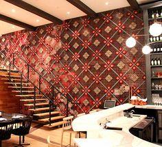 Parede de restaurante decorada com pontos cruz de tecido