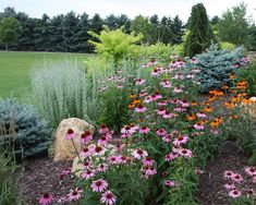 This is the style I'd like along the front of the property......I like the framework of evergreens, boulders but the casual look of the perennials scattered for summer color too.  Blooming shrubs wouldn't be a bad combo either. #rockgardenbordersflowerbeds (rock garden borders flower beds)