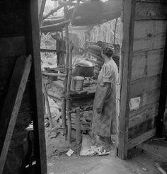 La esposa de un agricultor preparando la cena en el fogón de su casita en Caguas, Puerto Rico (1941)