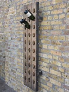Salvaged French oak riddling rack now wall-hung with metal brackets.