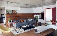 PEGADA MASCULINA O sofá é a peça principal do apartamento decorado pela arquiteta Andrea Reis. Nele, o morador Fabio Santos toca violão e assiste a jogos de futebol com os amigos. A base cinza ganhou charme com estampas geométricas, pontuadas em almofadas e objetos