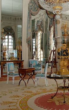 The Room of Mirrors in the Grand Trianon in the Palace of Versailles has a French Empire Aubusson rug with purplish red and gold on a cream ground. The drapes and chairs are in blue, silver and gold silk damask which balances the warm colors in the rug. Image © EPV, Jean-Marc Manaï and Pinterest Aubusson Rugs Style.