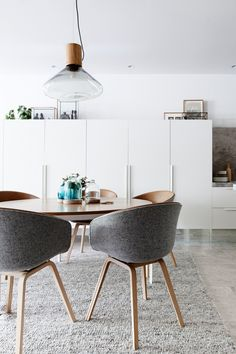 A 'Bronze' dining table by Melbourne designer Daniel Barbera is paired with upholstered 'About a Chair' bucket seats by Hay and a grey, text...