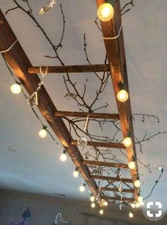Another idea for our wooden ladder. A vintage wooden ladder makes great lighting! This one is wrapped with globe lights, and decorated with vintage chandelier crystals and branches. There are endless variations on this theme!