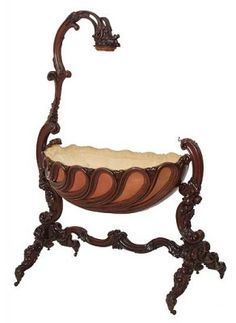 *Rococo Victorian mahogany swinging cradle on stand. it has a a beautiful elegant curved frame w/extensive floral carvings. There is a top pediment at one end + brass hook at the other that would have supported a valence + held a draped veil, c. 1850.