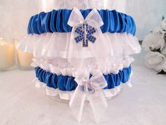 Your new EMT will share the ride of your life. This hand crafted wedding garter gift set is made with royal blue satin and white organza. The charm on the keep