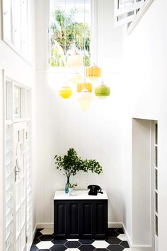 White entranceway/hallway with gallery wall, hanging yellow and green vintage lights