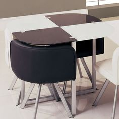 Perfect for smaller spaces and unique in style this compact dining table finished in Black and White with silver accents is sure to enhance your current d�cor.