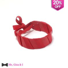 Red bracelet made of wooden tongue depressor and red ribbon.
