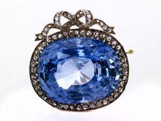 Wunderschöne, hochfeine Brosche mit großem, hellem Ceylon-Saphir, ca. 22,5 ct, umrahmt von Diamantrosen, zus. ca. 0,5 ct. Im originalen Londoner ...