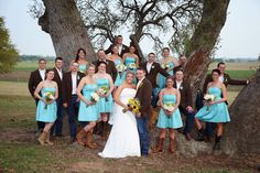 I love the aqua/turquoise bridesmaids dresses paired with the cowgirl boots! This picture is country wedding perfection! <3