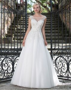 Illusion and hand beaded Sabrina neckline, crystal beaded bodice and full tulle skirt create a graceful gown that incorporates unique details.