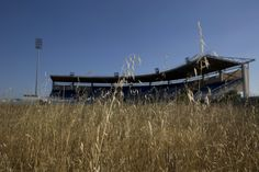 In this photo taken in July 2015, an abandoned stadium used for baseball events during the Athens Olympics is seen through weeds.