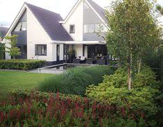 Een moderne tuin, waarin de strakke lijnen aansluiting vinden met het huis. ...