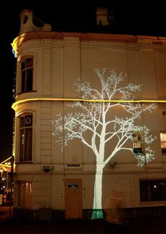 Tree, by Simon Heijdens, is projected onto several facades in the city, including dark corners and alleys. The main location has a 3x8 meter drawing of a tree projected onto the facade of a building. The branches and leaves move slightly, with an intensity that depends on actual wind gusts.