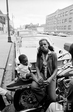 African American woman sitting on a motorcycle w. her child, part of the growing numbers of black motorcycle enthusiasts-- circa 1971.
