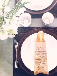 Dinner party menu written on a paper bag with an individual baguette for each guest