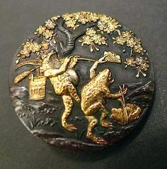 Bronze button depicting two toads. One with a wooden bucket hanging from a cattail, and the other dancing with a fan and a petal basket.