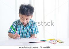 Portrait of Asian boy  is drawing using color pencil on white background - stock photo