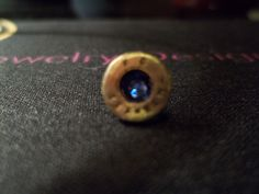 Bullet casing Tie/Lapel pin with Sapphire Blue Swarovski crystal. $20.00.