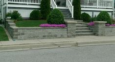 A stone block retaining wall and steps lead to the porch of this small sloped front yard.