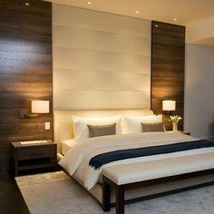 Quarto com cabeceira estofada e painel de madeira, luminária de parede lateral e criado mudo, spot
