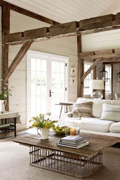 This living room employs clean touches in order to enliven an aged farmhouse interior. A Pottery Barn sofa slipcovered in washable canvas and a bolster pillow that's been hand stitched from a grain sack add new life to impressive exposed wood framing and support beams. Fresh white paneled walls welcome in lots of light. Using an old chicken crate as a base, a homemade coffee table helps retain genuine rustic appeal.