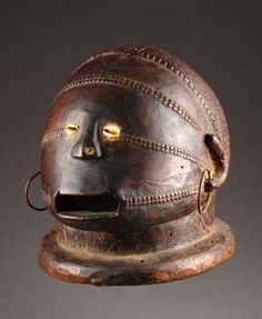 Africa | Helmet mask from the Tabwa people of DR Congo | wood, dark brown shy patina, cowrie shell eyes and metal