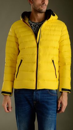 Ultra light down jacket in yellow featuring zip fastening with double puller, long sleeves, two zippered seam pockets, inner pockets, elasticized waistband, Velcro cuff closure, no detachable hood, removable polycarbonate lenses in silicone frame, mesh grate detailing ears and mouth, removable pompom, regular fit, 100% polyamide, padding 100% goose down feather.
