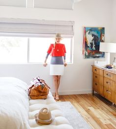 White walls, honey dresser, modern high windows with shades