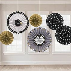 These Grad Paper Fan Decorations are black, gold and silver with stars and the white fan features a graduation hat in the center.