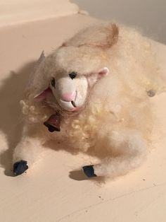 Wool felted sheep - resting Materials: Wool, wire armature, polymer clay, acrylic paint, matte varnish, rusty bell, twine rope