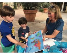 Tooth fairy game widens kids' cultural perspective. Featured photo: Tiffany Reimer shows the Passport 4 Change world map to two students.