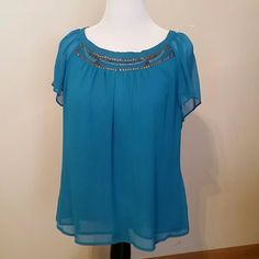 Detailed top Sheer top is lined and embellished with dainty bronze and silver. Sheer fluttery sleeves. Beautiful rich turquoise color. Nue Options Tops Blouses