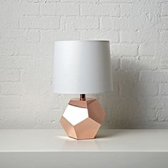 Shop Geometric Rose Gold Lamp.  If you're having a rocky time decorating your home, this table lamp will make things go a bit more smoothly.  It sports a rose gold base with a unique geometric design that will complement any room in the house.