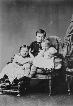 Da esquerda para a direita: Princesa Alix de Hesse, sentada; Príncipe Ernesto Luis de Hesse, sentado, com os braços ao redor de suas irmãs; Princesa Marie de Hesse, sentada ao lado de seu irmão na mesma cadeira. Ambas as meninas em vestidos de manga curta. Dezembro de 1875.