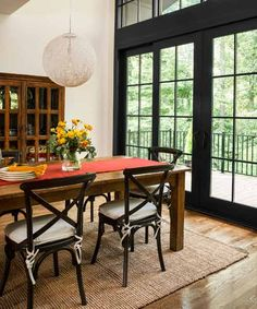 Oversize aluminum-clad patio doors echo the casements while framing the view in this dining room