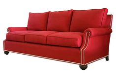 Here, a rolled-arm, red-linen sofa with loose cushions, carved bun feet and nailhead detailing.