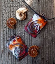 Ammonite Fossil Pendants Embossed copper spiral torch fired with white and orange and clear spasmodically and then finished with liver of sulphate patina. Sometimes it's nice to have a perfect even coat of enamel and other times I deliberately scrape bits back and over/under fire to get interesting textures and depth to a piece.