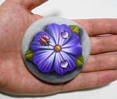 Hand painted stone ladybug with water drops on a beautiful