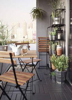 Petit balcon meublé avec une table pliante et trois chaises pliantes en acacia massif avec pieds en acier noirs. Une étagère en acier gris complète l'ensemble, garnie de plantes vertes dans des cache-pots galvanisés.