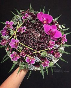 Round wedding bouquet with phalaenopsis orchids, carnations, dendrobium orchids in a European Oasis bouquet holder