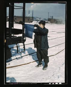 John Paulinski, car inspector, blue-flagging a train for inspection, at Corwith yard, Santa Fe RR trip, Chicago, Ill. March 1943. Photographed by Jack Delano. From the collection of the Library of Congress of the United States.
