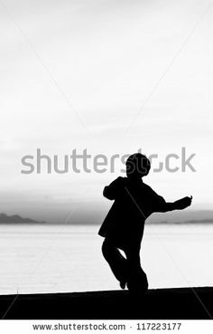 Silhouette taekwondo boy on the beach at dusk. Black and whit picture. by ARZTSAMUI, via Shutterstock